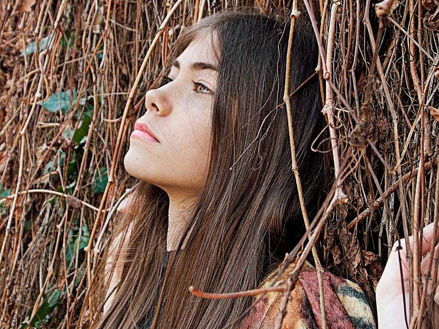 Chica con el pelo castaño largo liso entre ramas secas de otoño